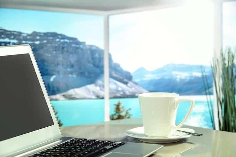 Zuhause mit Laptop und Kaffee, ein Home Solarium bringt das ganze Jahr über Sonne ins Eigenheim!
