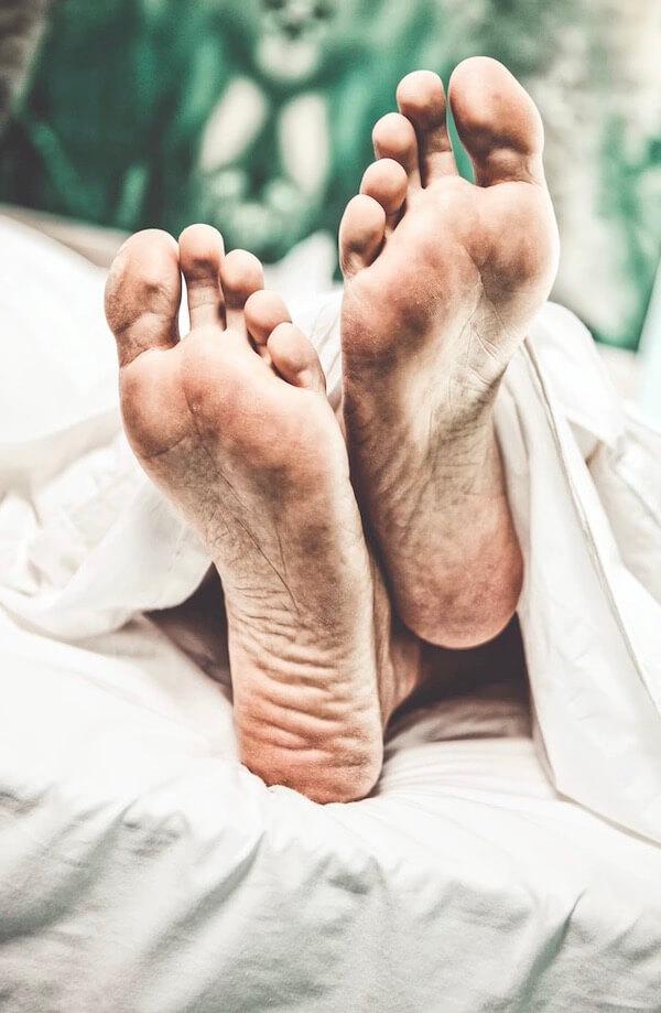 Füße eines Mannes im Bett
