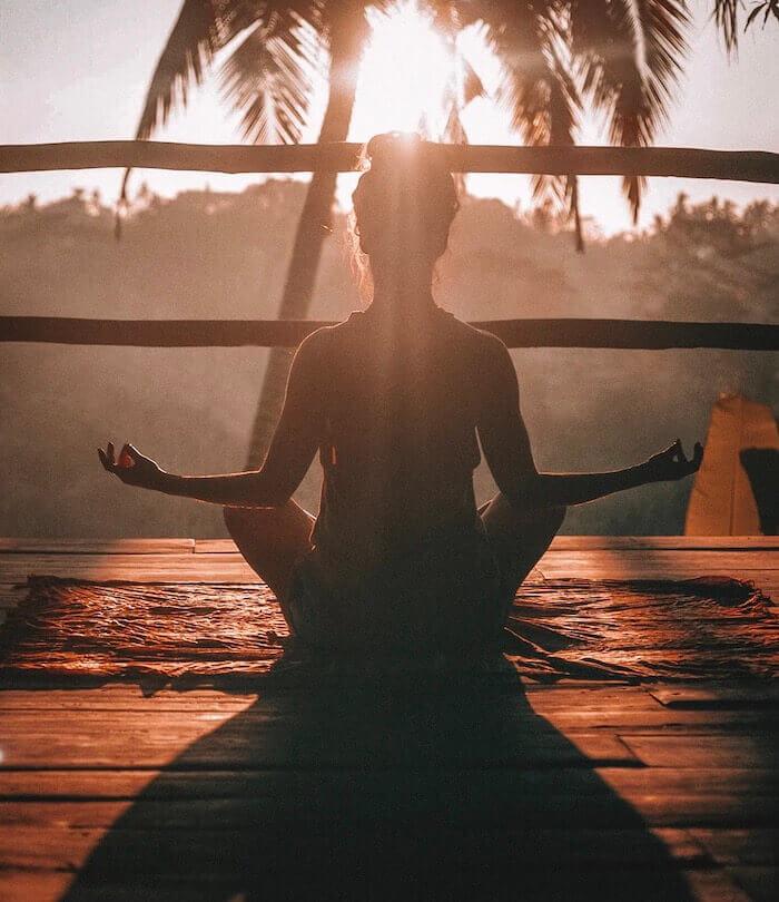 Lichttherapie, Frau sitzt in Jogaposition vor der Sonne