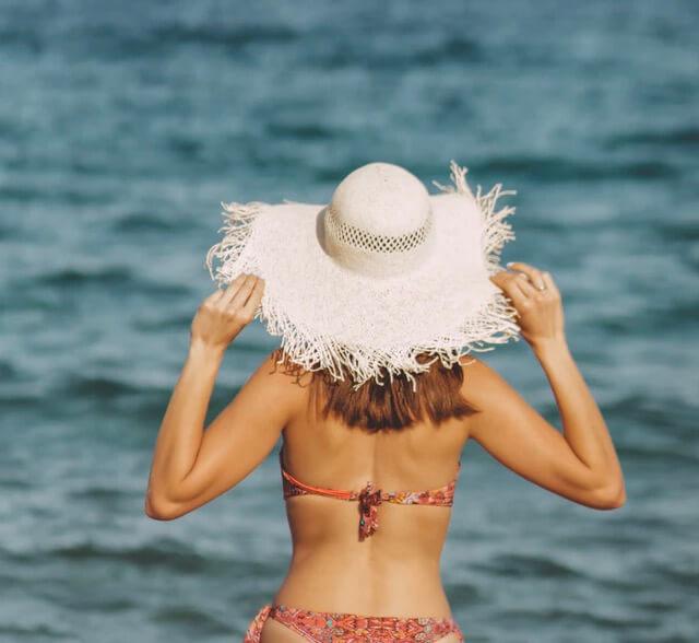 Frau im roten Bikini mit weißem Strohhut am Meer