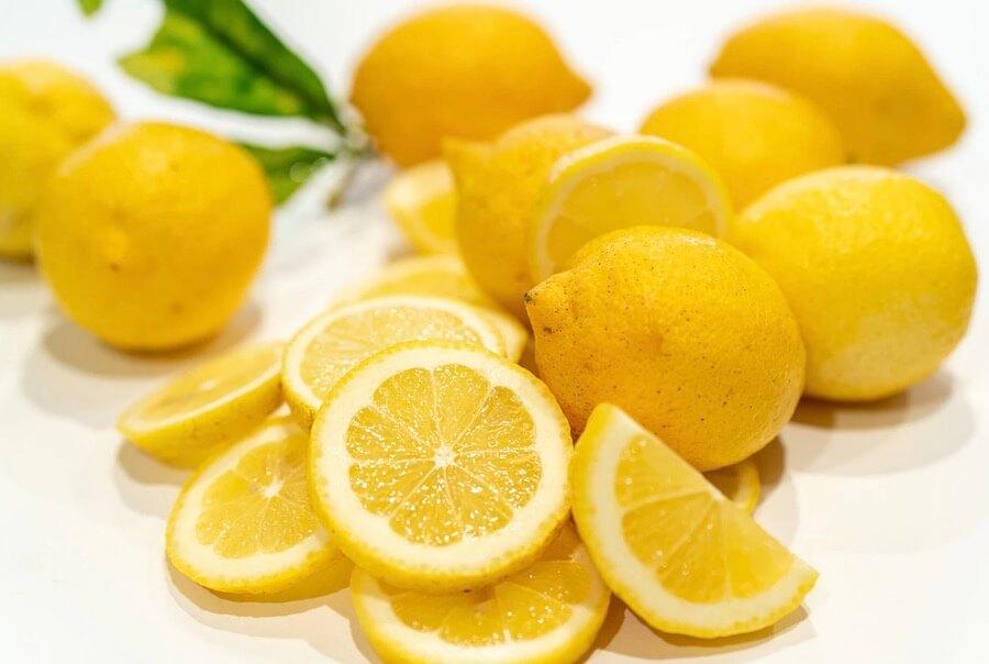 Zitronen im Ganzen und aufgeschnitten auf einem Tisch