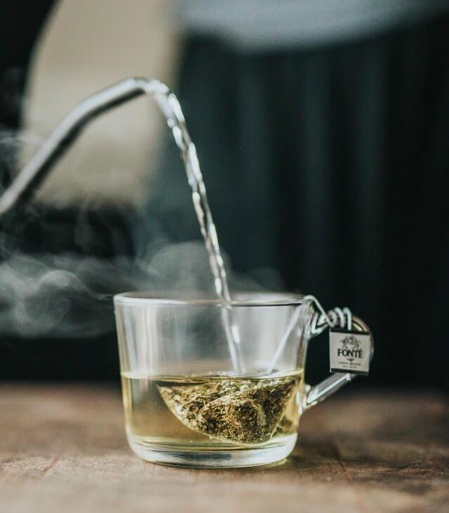 Teebeutel mit grünem Tee wird in einer Tasse mit kochendem Wasser übergossen.