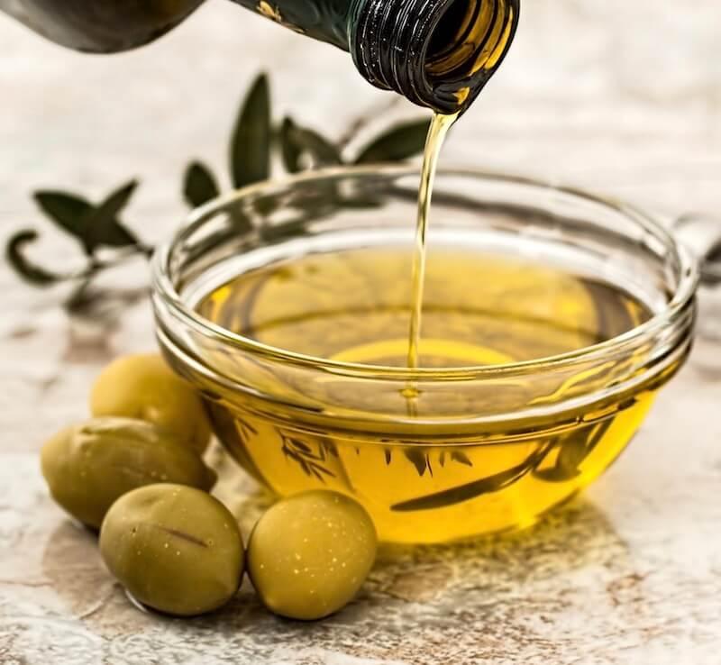Olivenöl wird von einer Flasche in eine Schale gegossen, daneben liegen Oliven und ein Olivenzweig