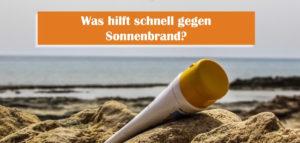 Sonnenbrand schnell loswerden, Sonnencreme-Tube liegt im Sand am Meer