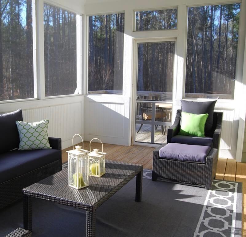 Wintergarten mit Sofa, Sessel und Tisch, auf die von außen die Sonne scheint.