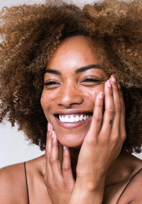 Frau die lacht mit braunen lockigen Haaren